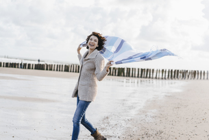 Happy woman with cloth on the beachの写真素材 [FYI04347930]