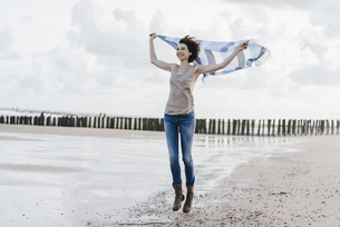 Happy woman with cloth on the beachの写真素材 [FYI04347931]