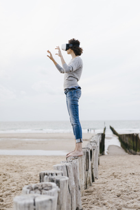 Woman standing on wooden stake on the beach wearing VR glassの写真素材 [FYI04347989]