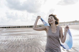 Happy woman with cloth on the beachの写真素材 [FYI04348006]