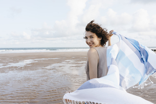 Happy woman with cloth on the beachの写真素材 [FYI04348007]