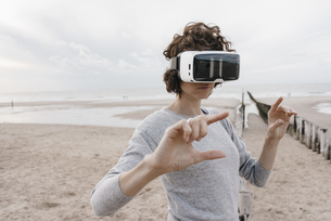 Woman on the beach wearing VR glassesの写真素材 [FYI04348060]