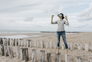 Woman standing on wooden stakes on the beach wearing VR glasの写真素材 [FYI04348061]