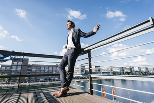 Happy businessman standing on balcony, with arms outの写真素材 [FYI04348078]