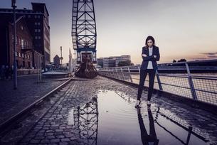 Businesswoman standing at wet inner harbor, thinkingの写真素材 [FYI04348085]