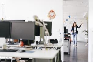 Happy businesswoman juggling balls in officeの写真素材 [FYI04348105]