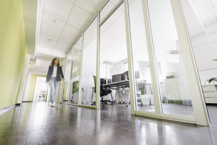 Businesswoman walking in corridor of office buildingの写真素材 [FYI04348110]