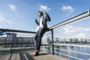 Happy businessman standing on balcony, with arms outの写真素材 [FYI04348126]
