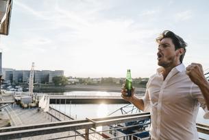 Happy businessman standing on balcony, drinking beerの写真素材 [FYI04348164]
