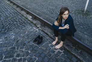 Barefoot businesswoman sitting on railの写真素材 [FYI04348168]