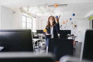 Happy businesswoman juggling balls in officeの写真素材 [FYI04348190]