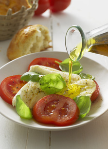Olive oil pouring on caprese salad in plate, close upの写真素材 [FYI04348343]