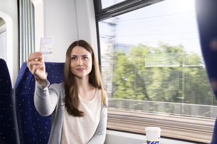 Germany, Brandenburg, Mid adult woman showing ticket, smilinの写真素材 [FYI04348632]