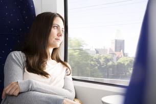 Germany, Brandenburg, Mid adult woman looking through windowの写真素材 [FYI04348634]