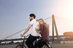 Happy couple riding bicycle on riverbankの写真素材 [FYI04348883]