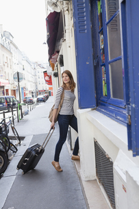 France, Paris, portrait of young woman with rolling suitcaseの写真素材 [FYI04348941]