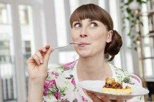 Smiling woman enjoying piece of cakeの写真素材 [FYI04349235]