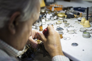 Watchmaker in foreground while working with a wristwatchの写真素材 [FYI04349990]