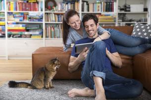 Adult couple lying on sofa, using digital tabletの写真素材 [FYI04350030]