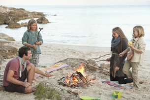 Spain, Mallorca, Friends grilling sausages at camp fire on bの写真素材 [FYI04350884]