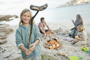 Spain, Mallorca, Friends with sausages at camp fire on beachの写真素材 [FYI04350885]