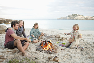 Spain, Mallorca, Friends grilling sausages at camp fire on bの写真素材 [FYI04350886]