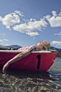 Germany, Bavaria, Mid adult man sleeping in rowing boatの写真素材 [FYI04350921]