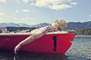 Germany, Bavaria, Mid adult man sleeping in rowing boatの写真素材 [FYI04350922]