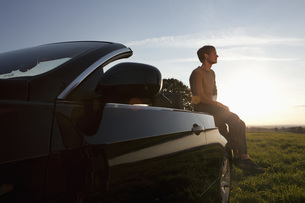 Germany, Bavaria, Mid adult man sitting on carの写真素材 [FYI04351012]