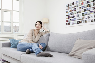 Germany, Bavaria, Munich, Mid adult woman sitting on couch,の写真素材 [FYI04351102]