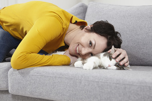Germany, Bavaria, Munich, Mid adult woman with cat on couch,の写真素材 [FYI04351107]