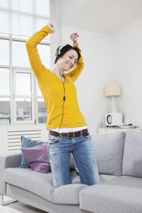 Germany, Bavaria, Munich, Mid adult woman listening music onの写真素材 [FYI04351108]