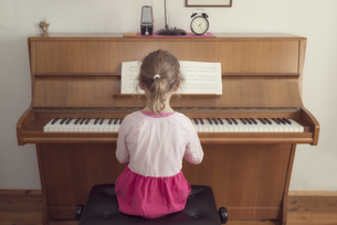 Little girl playing piano at homeの写真素材 [FYI04351874]