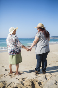 Grandmother and adult granddaughter holding hands on the beaの写真素材 [FYI04352480]