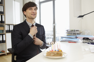 Germany, Cologne, Mid adult man with birthday cake, smilingの写真素材 [FYI04353102]