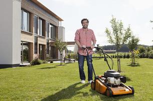 Germany, Bavaria, Nuremberg, Mature man with lawn mower in gの写真素材 [FYI04353248]