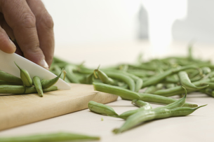 Mid adult man cutting string beans on wooden board with ceraの写真素材 [FYI04353260]