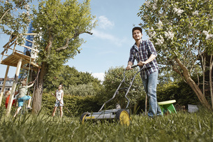 Man mowing lawn in garden with family in backgroundの写真素材 [FYI04353820]