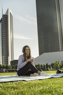 Germany, Frankfurt, young woman sitting on blanket on a meadの写真素材 [FYI04353849]