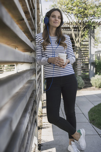 Portrait of smiling woman with coffee to go hearing music wiの写真素材 [FYI04353851]