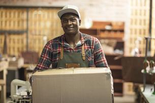Portrait of smiling man carrying cardboard box in workshopの写真素材 [FYI04354989]