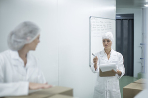 Woman with clipboard instructing worker in factoryの写真素材 [FYI04355130]