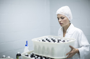 Woman carrying box of medical supplies in medical factoryの写真素材 [FYI04355132]