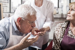 Senior man smelling seeds from chef's hand in cooking classの写真素材 [FYI04355397]