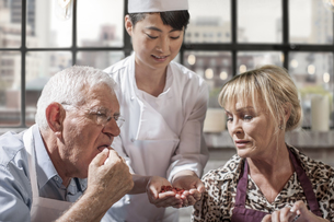 Senior couple tasting seeds in cooking classの写真素材 [FYI04355399]