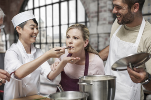 Female student tasting from pot in cooking classの写真素材 [FYI04355406]
