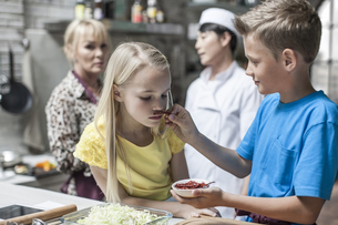 Children smelling chili in cooking classの写真素材 [FYI04355421]