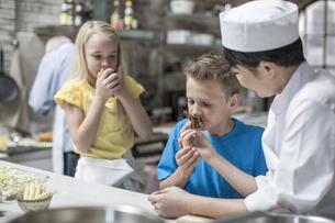 Boy and girl smelling food from female chef in cooking classの写真素材 [FYI04355426]