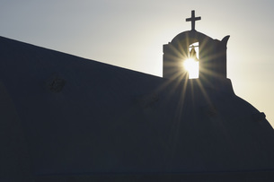 Greece, Sun shines through belltower in Oia village at Santoの写真素材 [FYI04355983]