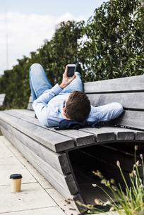 Young man lying on bench using smart phoneの写真素材 [FYI04357151]